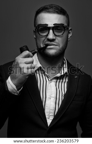 Man with a smoking pipe in sunglasses - stock photo