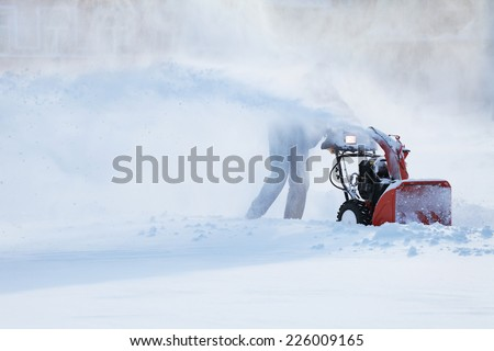 man with a snow blowing machine working in winter day - stock photo