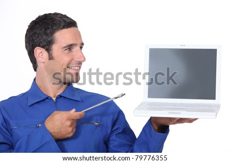 Man with a spanner and laptop computer - stock photo