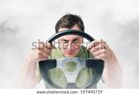 Man with a steering wheel in smoke, auto concept - stock photo