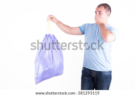 Man with a stinking garbage bag in hand on white background