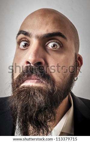 man with a suit and beard and strange expressions on white background - stock photo