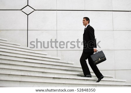 Man with a suitcase lifting stairs - stock photo