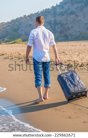 man with a suitcase walking along the beach - stock photo