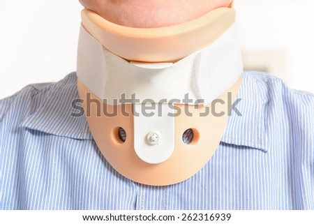 Man with a surgical cervical collar suffering from neck pain - stock photo