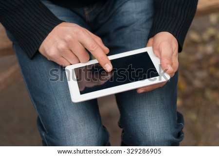 Man with a tablet in his hand close-up on the street. - stock photo