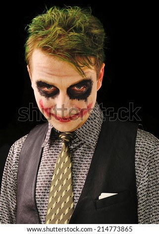 Man with a terrible make-up on black background - stock photo