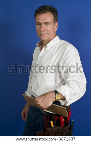 Man with a tool belt around his waist and a clipboard in his hand taken in front of a blue backdrop.