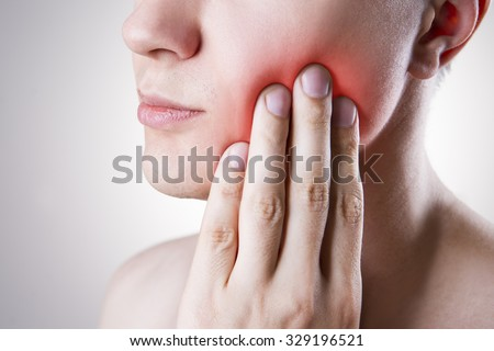 Man with a toothache. Pain in the human body on a gray background with red dot