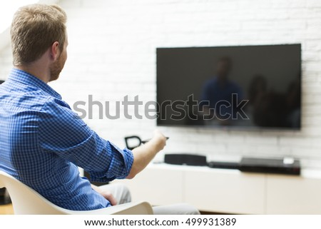 Man with a tv remote control sitting in a living room