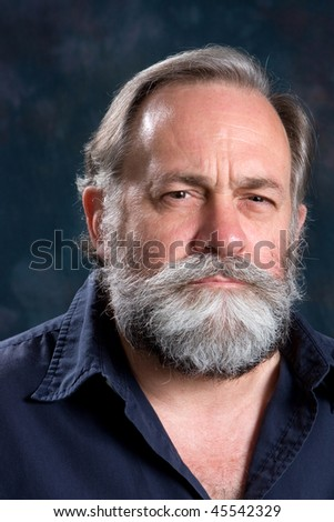 Man with a wary look is somewhat suspicious of what he sees with squinted eyes. - stock photo