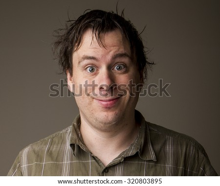 Man with a weird but happy wide eyed smile - stock photo