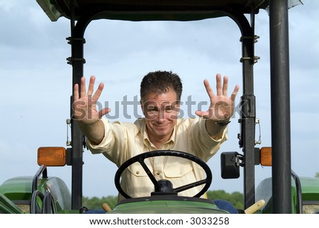 Man with a worried smile sitting on a tractor gesturing for someone to stop. - stock photo