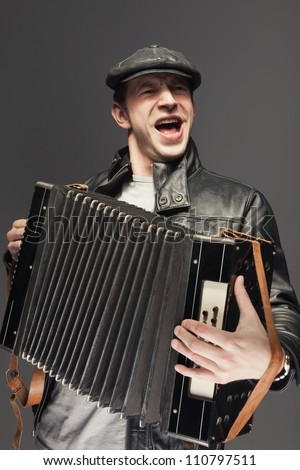 Man with accordion. Man is singing songs and playing the old accordion - stock photo