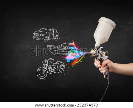 Man with airbrush spray paint with car, boat and motorcycle drawing on dark background - stock photo