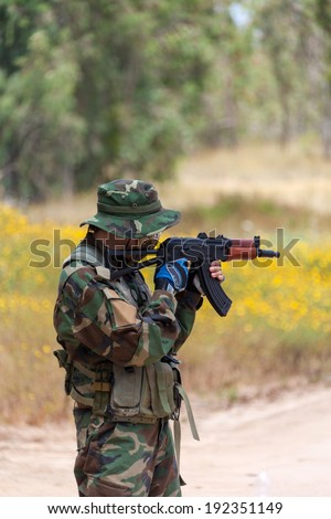 man with AK holds at gunpoint, the military conflict