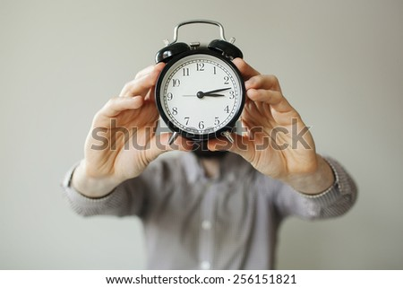 Man with alarm clock head in hands over white background - stock photo