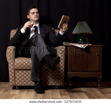 Man with alcohol sitting in vintage armchair - stock photo