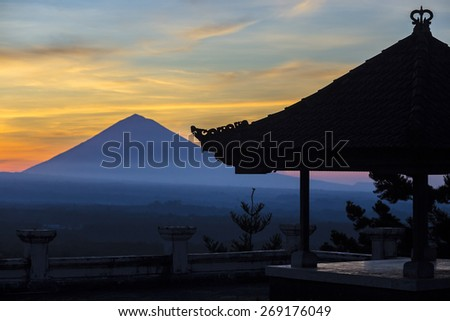 Man with and Volcano Agung as Background at Sunrise Time,Bali,Indonesia.