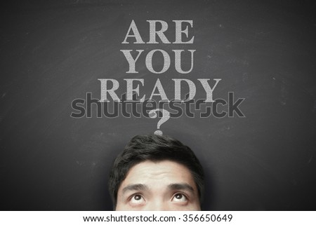 Man with Are you ready concept on the blackboard background. - stock photo