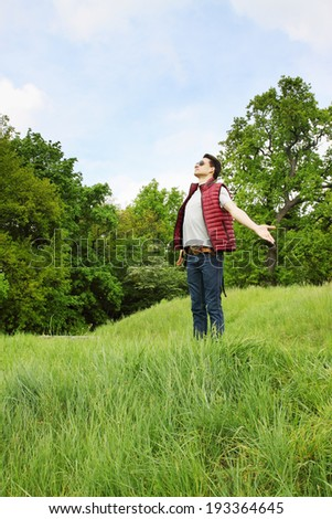Man with arms outstretched on the nature - stock photo