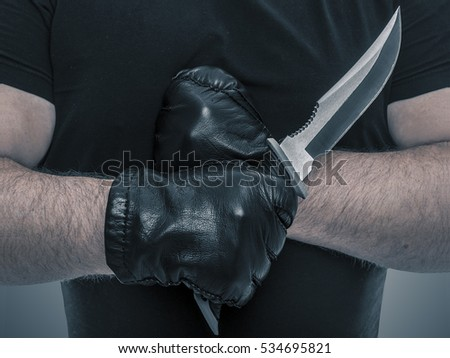 Man with athletic hands holding a military knife. Close-up.
