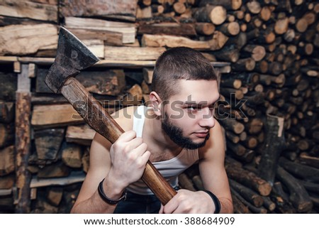 Man with ax in hands near firewood stock, focus on ax - stock photo