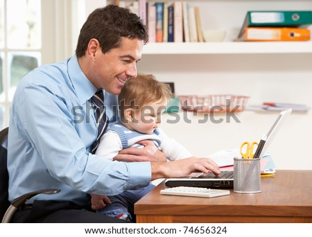 Man With Baby Working From Home Using Laptop - stock photo