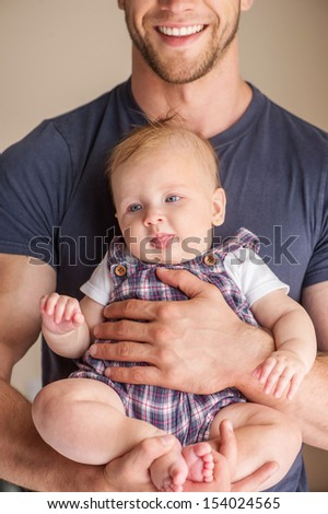 Man with baby. Young muscular man holding baby in his hands and smiling
