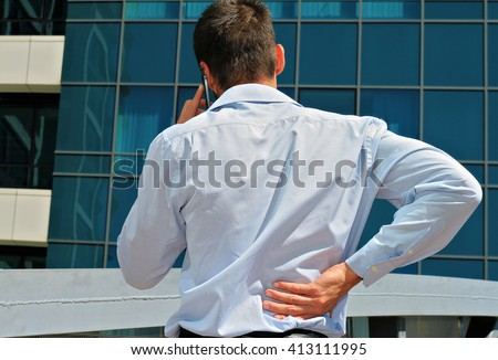 Man with  back pain. Business man rubbing his painful low back - stock photo