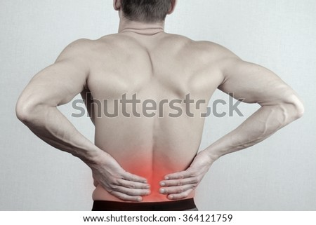 Man with  back pain. Man rubbing his painful back close up. Pain relief concept - stock photo