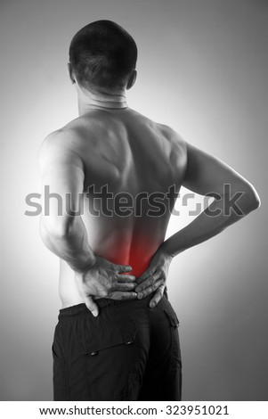 Man with backache. Pain in the human body. Black and white photo with red dot - stock photo