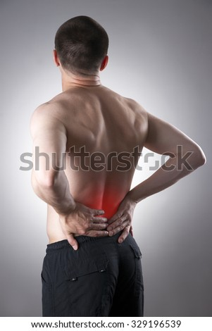 Man with backache. Pain in the human body on a gray background with red dot - stock photo