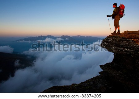 Man with backpack high above the misty mountain valley - stock photo