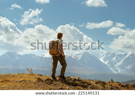 Man with backpack standing on a background of mountains