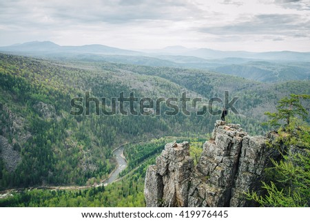 Man with backpack standing on top of the mountain with raised hands - stock photo