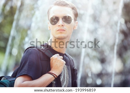 Man with bag travelling in the city near public fountain - stock photo