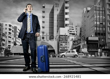 Man with baggage speaking by phone on the crossroad  - stock photo