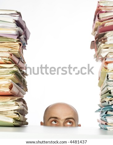 Man with bald head peaks above desk to see stacks of files and folders waiting for his attention. - stock photo