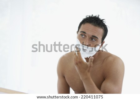 Man with bare chest applying shaving cream to face