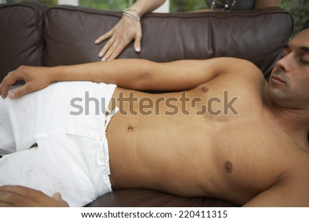 Man with bare chest sleeping on sofa - stock photo