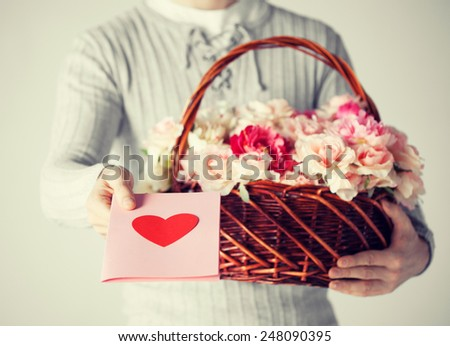 man with basket full of flowers and giving postcard. - stock photo