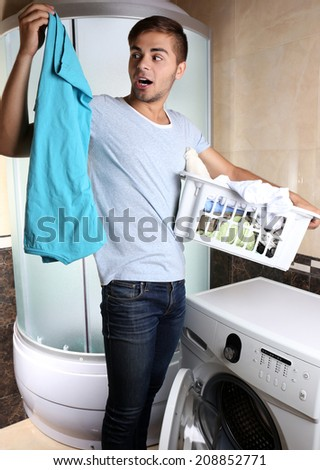 Man with basket of laundry, indoors  - stock photo