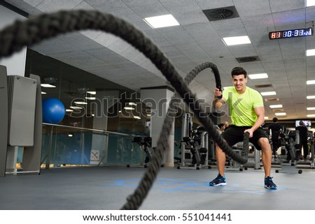 Man with battle ropes exercise in the fitness gym. Young male wearing sportswear.
