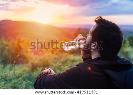 Man with beard drinking water from plastic bottle and enjoying mountain sunset. He is waring black backpack and black sport sweater. - stock photo