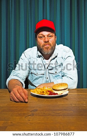 Man with beard eating fast food meal. Enjoying french fries and a hamburger. Trucker with red cap.