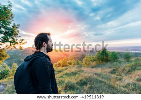 Man with beard enjoying mountain sunset and looking at the distance. He is waring black backpack and black sport sweater. - stock photo
