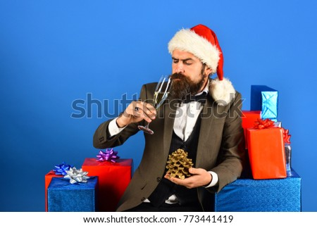 Man with beard holds cone and champagne. Santa in retro suit near blue and red gifts on blue background. Businessman with serious face holding golden cone and glass of drink. Christmas concept