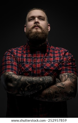 Man with beard in color shirt and tattooes on his hands posing in studio. Isolated on black. - stock photo