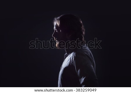 Man with  beard, profile  on  dark background, the silhouette.  - stock photo